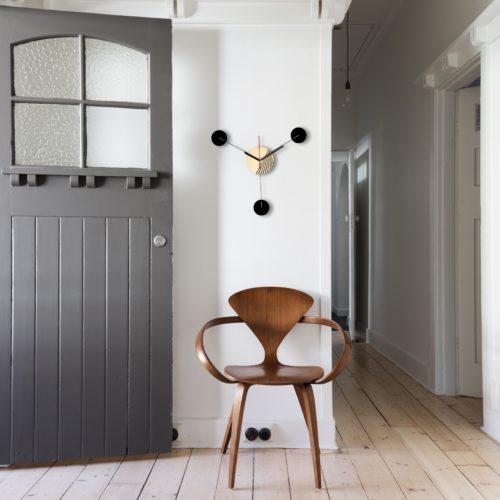 Horloge Murale Personnalisable Trio composée d'un disque de bois gravé et de trois pales d'acier laquées Noires Dans Une Entrée Vintage | Virvoltan