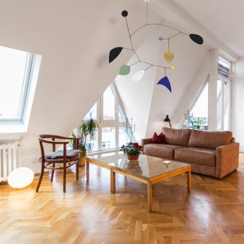 Mobile Calder Personnalisable Bleu Klein Vert Amande et Noir Dans Un Salon Sous Pente Avec Parquet | Virvoltan