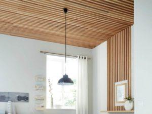 Un Plafond décoré de tasseaux qui se prolongent sur le mur